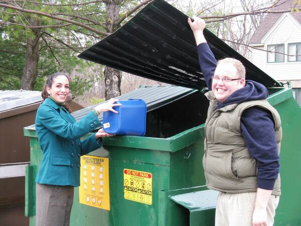 Green Grads Using Recycling Dumpster
